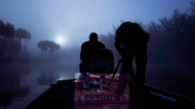 Picture Shows: Behind the scenes. Dawn on a winter's morning in the southern swamps of Florida. Cameraman Howard Bourne checks his camera to line up a shot. By gliding slowly on a boat the team were able to capture smooth tracking footage through the eery, steaming landscape. Beneath them alligators and manatees make their way to hot-springs to escape the chilly waters.